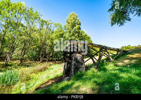 Old water mill on a meadow with green grass and blue sky in the summer - Stock Image
