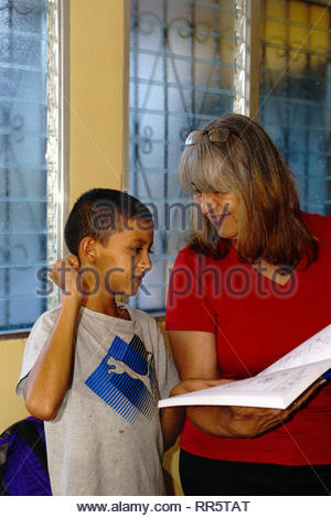NGO employee and deaf boy look at a dictionary of Nicaraguan Sign Language at a shelter for the deaf in Jinotega, Nicaragua. - Stock Image