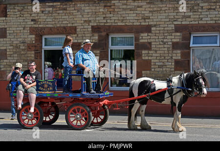 Gypsy Traveller family riding on cart. Appleby Horse Fair 2018. The Sands, Appleby-in-Westmorland, Cumbria, England, United Kingdom, Europe. - Stock Image