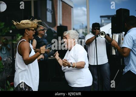 Puerto Ricans dance during a Thanksgiving event in an area hard hit by Hurricane Maria November 22, 2017 in Caguas, - Stock Image