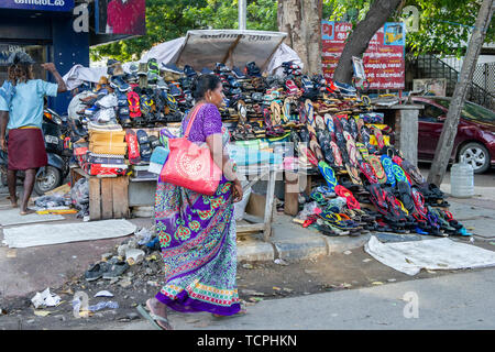Poverty in Chennai, India, where street stalls and street sellers on the side of the road are common. This one with a mountain of coloured shoes - Stock Image