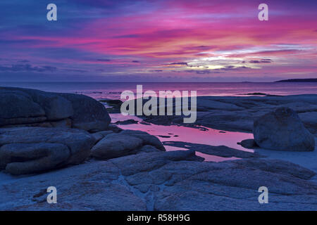 Beautiful pink and purple hues of sunrise at Cosy Corner South in Bay of Fires in Tasmania. - Stock Image