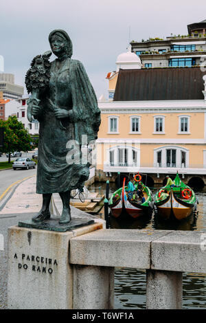 Aveiro, Portugal - April 29, 2019: Iron statue next to a canal and Moliceiros in Aveiro, Portugal - Stock Image
