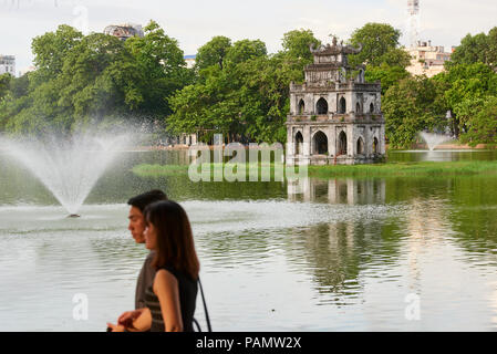 A couple strolls in front of Turtle Tower in Hoan Kiem Lake, central Hanoi, Vietnam. - Stock Image