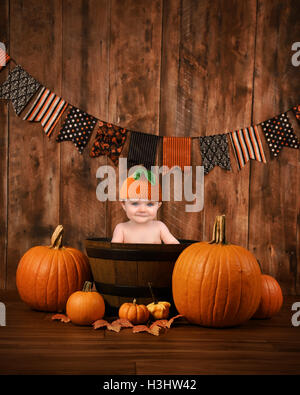 A little cute baby is sitting in a wood basket with halloween fall pumpkins around the child for a seasonal portrait - Stock Image