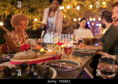 Friends enjoying candlelight dinner garden party - Stock Image