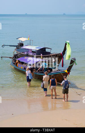 People getting onto a long tail boat going to Railay, Ao Nang, Krabi province, Thailand - Stock Image