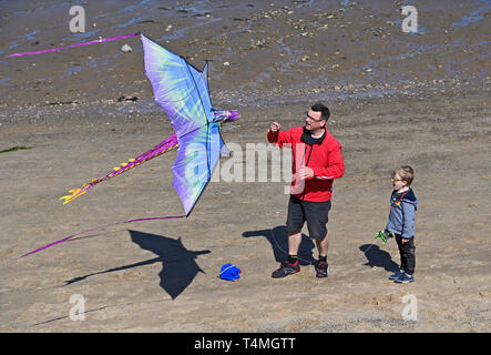 Father and son flying a kite on the beach. Morecambe, Lancashire, England, United Kingdom, Europe. - Stock Image