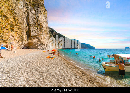 Tourists enjoy the sandy Paradise Beach, also known as Chomi Beach in Corfu, Greece, as a boat waits for tourists in the hidden cove - Stock Image