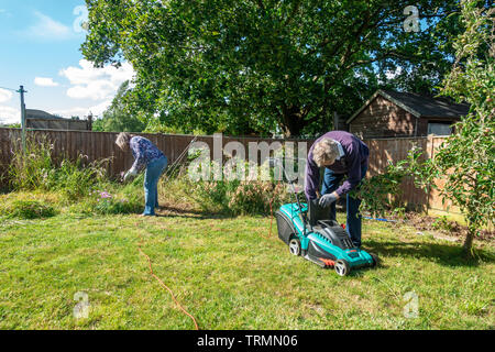 A retired couple doing some gardening in a residential garden. The lady does some weeding while the man mows the lawn with an clectric lawnmower. - Stock Image
