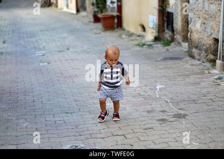 Cute Baby Boy Walking Alone In The Street In The Old Town Of Castellar On The French Riviera, France, Europe - Stock Image
