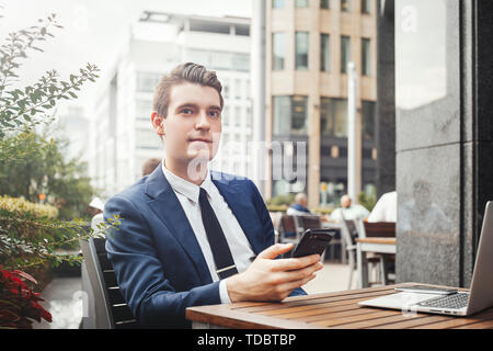 Young businessman sitting next to laptop, holding mobile phone in hand and looking aside. - Stock Image