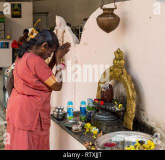 Woman Praying in front of Shiva Lingam before Entering Hindu Sri Maha Muneswarar Temple, Kuala Lumpur, Malaysia. - Stock Image