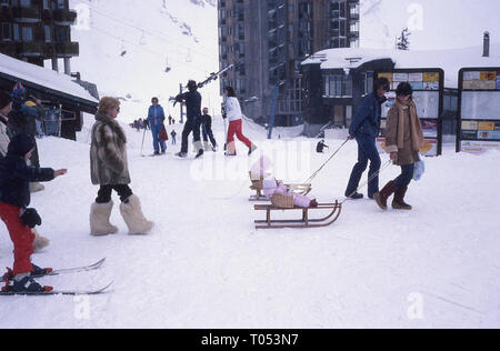 1960s, couple pulling their infant children sitting in baskets on sledges. - Stock Image