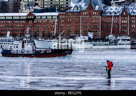 The frozen bay of Lake Malaren in the city centre with an ice skater watching a boat crash through the ice nearby at Stockholm, Sweden. Stockholm, Sweden. 21st January, 2019. - Stock Image