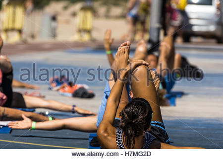 Women doing crunches during a fitnees class outdoor on a sunny day - Stock Image