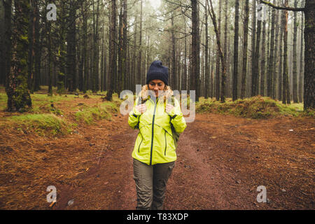 Happy hiker travel in the high trees wild beautiful forest with backpack - enjoying natural wood for pretty blonde young woman - adventure and trekkin - Stock Image