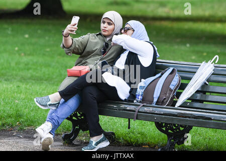 London, UK. 10th August, 2017. Two women take a selfie in Kensington Gardens as they enjoy the dry weather this morning in London, UK. Credit: BSFUK/Alamy Live News. - Stock Image