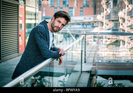 One attractive man in city environment wearing cardigan - Stock Image