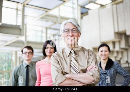 A portrait of a mixed race team of business people standing in the lobby area of a convention center with an Asian businessman in the lead. - Stock Image