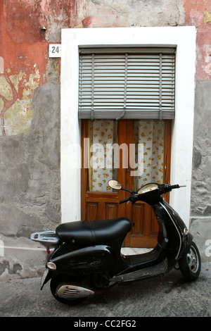 A black scooter parked outside of a small Italian door in Sicily, Italy. - Stock Image