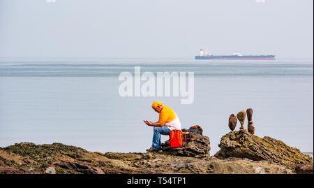Dunbar, East Lothian, Scotland, UK. 21st Apr 2019. European stone stacking championship:  Balanced stones at Eye Cave beach by Dicey Turnbull from Bonnyrigg in Scotland, as he takes a rest on the second day which comprises 2 competitions, a 3 hour artistic challenge and a children's competition. The overall winner receives a trip to llano Earth Art Festival & World Stone Balancing competition in Texas in 2020. Credit: Sally Anderson/Alamy Live News - Stock Image