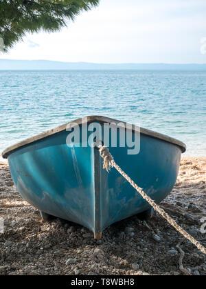 Small blue boat on the beach close to the sea in Tucepi, Croatia - Stock Image