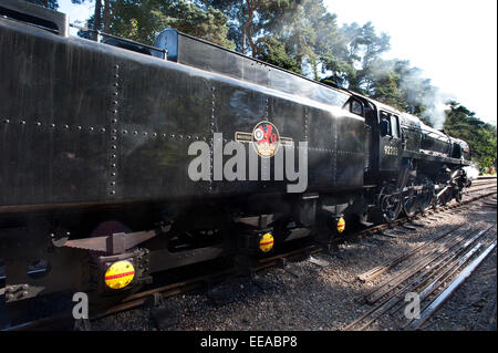 The driver of 9F 2-10-0 Steam Locomotive number 92203 'Black Prince' checks the road ahead as it runs round - Stock Image
