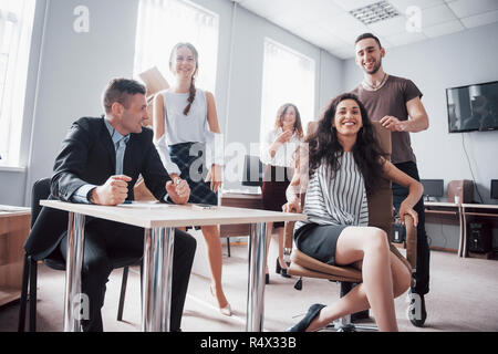 A group of business people celebrating, having fun, at the office. - Stock Image
