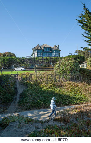 People stroll along Monterey Bay Coastal Trail and Ocean View Blvd., beneath stately home in Pacific Grove, California, - Stock Image