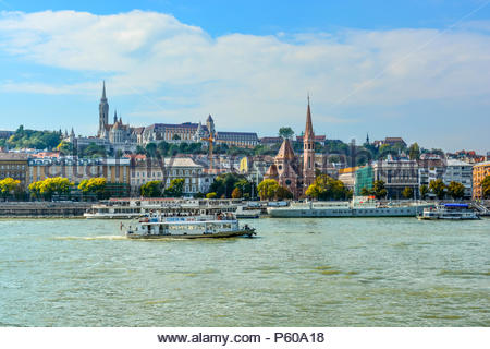 The Szilágyi Dezso Square Reformed Church on the banks of the Danube River in Budapest Hungary with the Castle District, St Matthias Church above - Stock Image