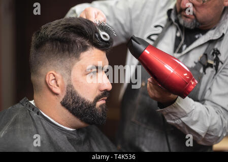 Close up view of master barber doing hairstyle with hairdryer at barber shop . - Stock Image