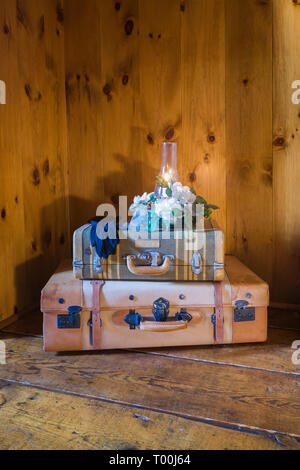 Lit candle on top of suitcases on hemlock wood plank flooring in upstairs master bedroom  inside an old circa 1760 Canadiana fieldstone home - Stock Image