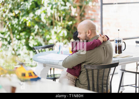 Affectionate father and son hugging at table - Stock Image