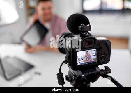 camera recording video blogger with tablet pc - Stock Image