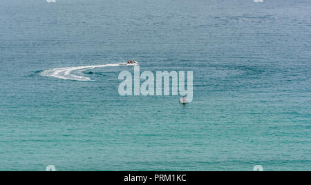 Jet Ski rides and hires at Newquay, Cornwall, the Jet Skis seen in blue sea waters. - Stock Image
