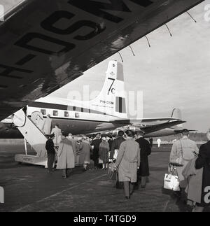 1960s, historical, passengers boarding a KLM Royal Dutch Airlines Douglas 7C plane at Alaska airport . As can be seen, in this era the the wording 'Koninkluke Luchtvaart Mu. Holland' was on the aircraft. - Stock Image