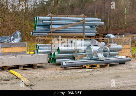 FLODA, SWEDEN - NOVEMBER 21 2018: Many new shiny corrugated sheet iron metal tubes stored on shelves on construction site ahead of being used - Stock Image