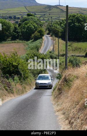 Car on narrow Welsh country road, Llanllyfni, Gwynedd - Stock Image