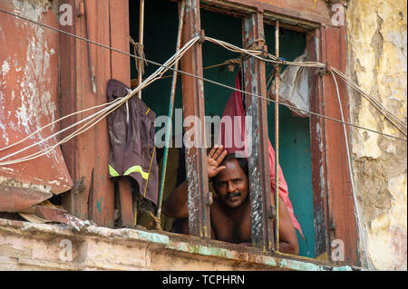 Poverty in Chennai, India, where a man waves from his bedroom window - Stock Image