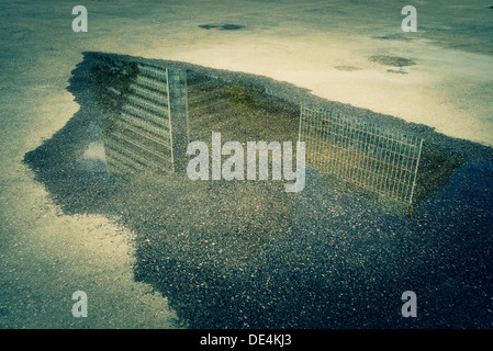 Skyscraper reflection in a puddle on the pavement - Stock Image