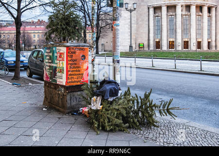 Berlin, Mitte  Street view with trashed Christmas trees, posters & facade of Volksbuhne Theatre - Stock Image
