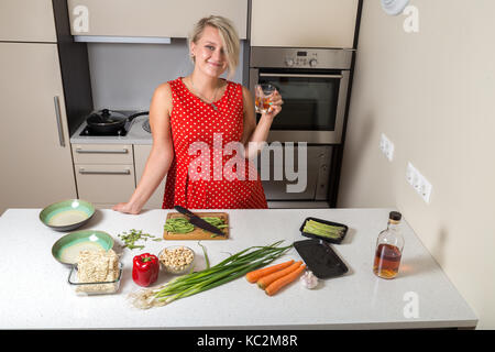 Adult girl holding whiskey glass in hand and smiling - Stock Image