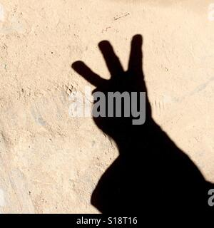 Counting with fingers - three - Stock Image