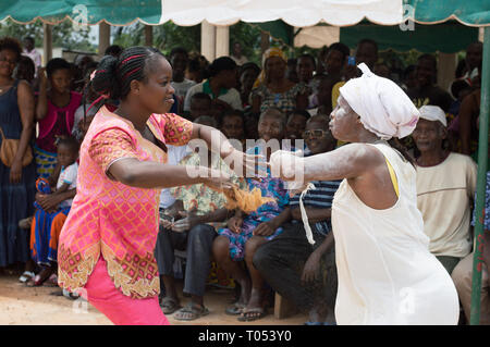 adzopé, ivory coast-aug. 31, 2016: young women dressed in white and the other in pink, both dancing face to face in the background of people under a b - Stock Image