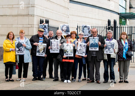 Families of those who died in the Ballymurphy Massacre hold images of those who died outside Laganside Court in Belfast as the inquest continues into the series of incidents between 9 and 11 August 1971, in which the 1st Battalion, Parachute Regiment killed eleven civilians in Ballymurphy, Belfast. - Stock Image