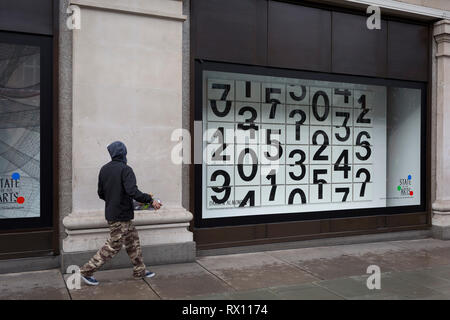 A skateboarder walks past a window display that features numbers - part of a design theme called 'State of the Arts', at the Selfridges department store on Oxford Street, on 4th March 2019, in London England. Darren Almond's piece 'Chance Encounter 004', consists of a grid formed from rectangular panels, featuring fragmented numbers that appear to scroll across the surface. State of the Arts is a gallery of works by nine crtically-acclaimed artists in Selfridges windows to celebrate the power of public art. - Stock Image