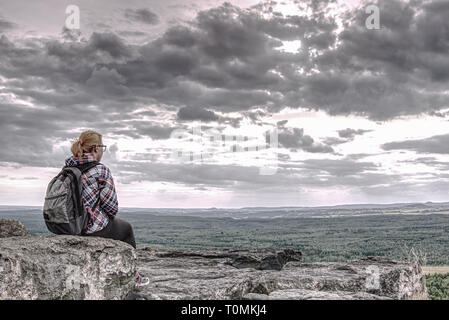 Blonde girl sits alone at edge  above the abyss in the mountains and looking out into the clouds on the peaks of the hills - Stock Image