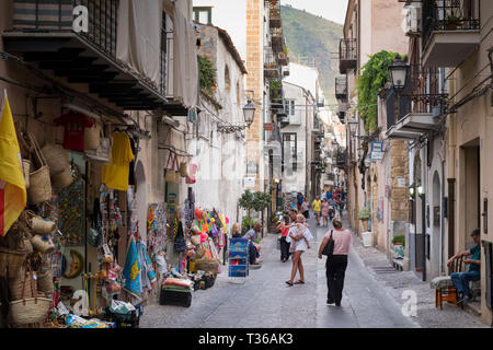 Street scene and souvenir shops in coastal town of Cefalu with Baroque style architecture in Northern Sicily, Italy - Stock Image