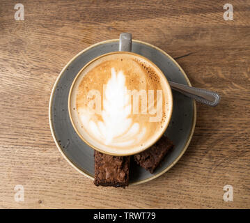 A cup of flat white coffee with chocolate brownies and a spoon on a saucer against a wood effect background, England, UK - Stock Image